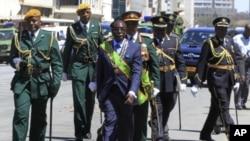 Robert Mugabe deixa o o edifício do Parlamento, ladeado pelos militares