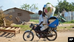 A couple flees on motorbike from the Jabel area of Juba, South Sudan, July 16, 2016. The United Nations refugee agency reports 26,000 people have left the country this month.