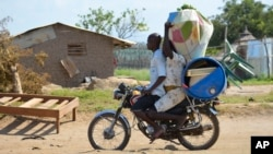 A couple flees on motorbike from the Jabel area of Juba, South Sudan, July 16, 2016. The United Nations refugee agency reports 26,000 fearful people have left the country this month.