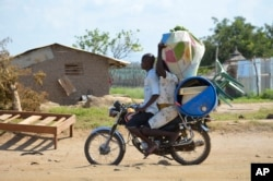 FILE - A couple flees on motorbike from the Jabel area of Juba, South Sudan, July 16, 2016. More than 25,000 fearful people have left the country this month, UNCHR says..