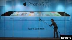Seorang pekerja membersihkan jendela di depan reklame iPhone 5C di Kunming, provinsi Yunnan, China (foto: dok).