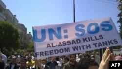"""Протестующие держат транспарант с надписью: """"ООН - СОС! Танки Асада (президент Сирии - """"Голос Америки"""") убивают свободу""""."""