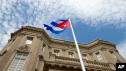 FILE - The Cuban flag is raised over their new embassy in Washington, July 20, 2015.