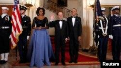 El presidente francés, Francois Hollande, saluda en la Casa Blanca, donde le fue ofrecido un banquete de Estado. Le acompañan la primera dama Michelle Obama y el presidente Barack Obama.