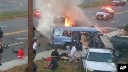 Des flammes s'échappent d'un véhicule après un accident mortel dimanche 8 novembre 2015, à Hyattsville, MD, Etats-Unis. (Steve Ramsey via AP)