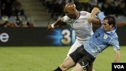 Nicolas Anelka berusaha merebut bola dari Diego Godin dalam pertandingan grup A Piala Dunia antara Uruguay dan Perancis di Cape Town. FFF menjatuhkan sanksi bagi Anelka atas ucapannya kepada pelatih pada partai melawan Meksiko.