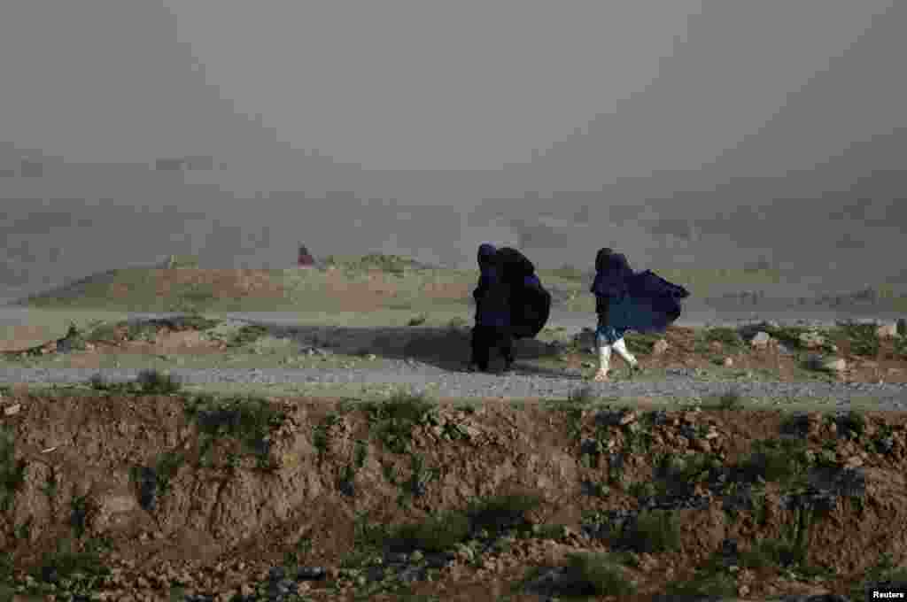 Women walk on a windy day outside Kabul, Afghanistan.