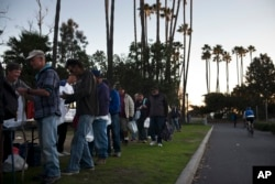 Homeless people wait in line for a free meal in Dana Point, California, Dec. 21, 2017.