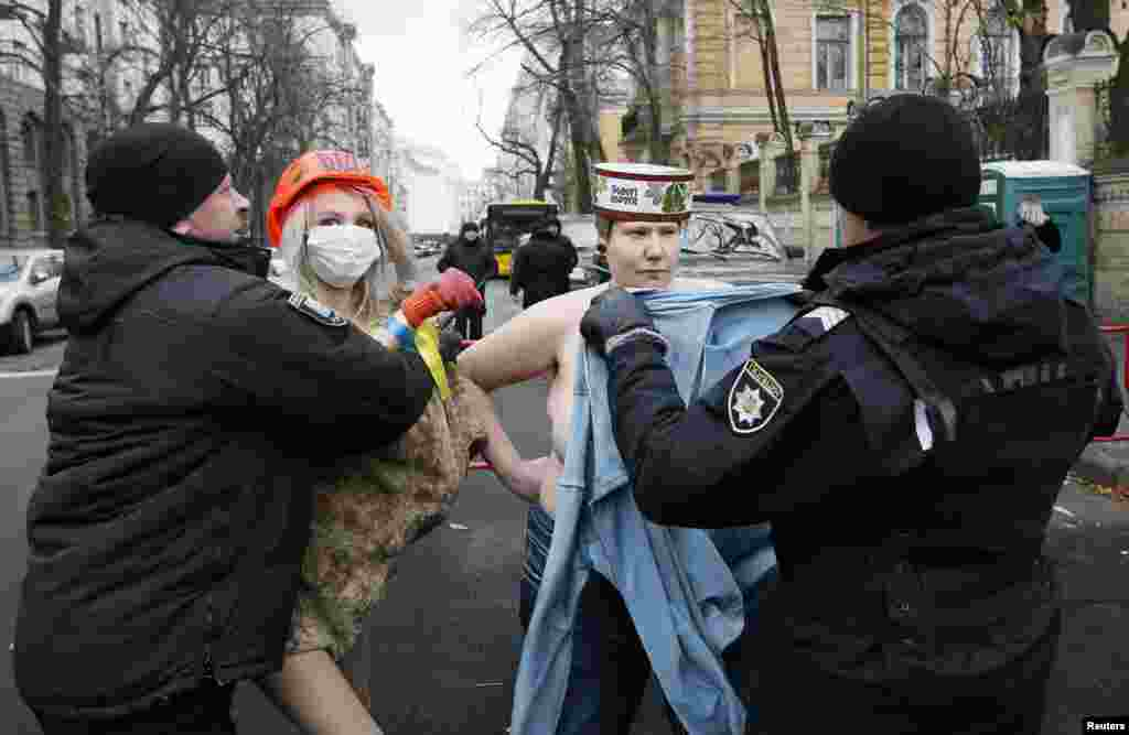 Policemen detain topless activists of women's rights group Femen, during a protest against Ukrainian President Petro Poroshenko and the government, while marking a Day of Dignity and Freedom, near the presidential administration headquarters in Kyiv, Ukraine.