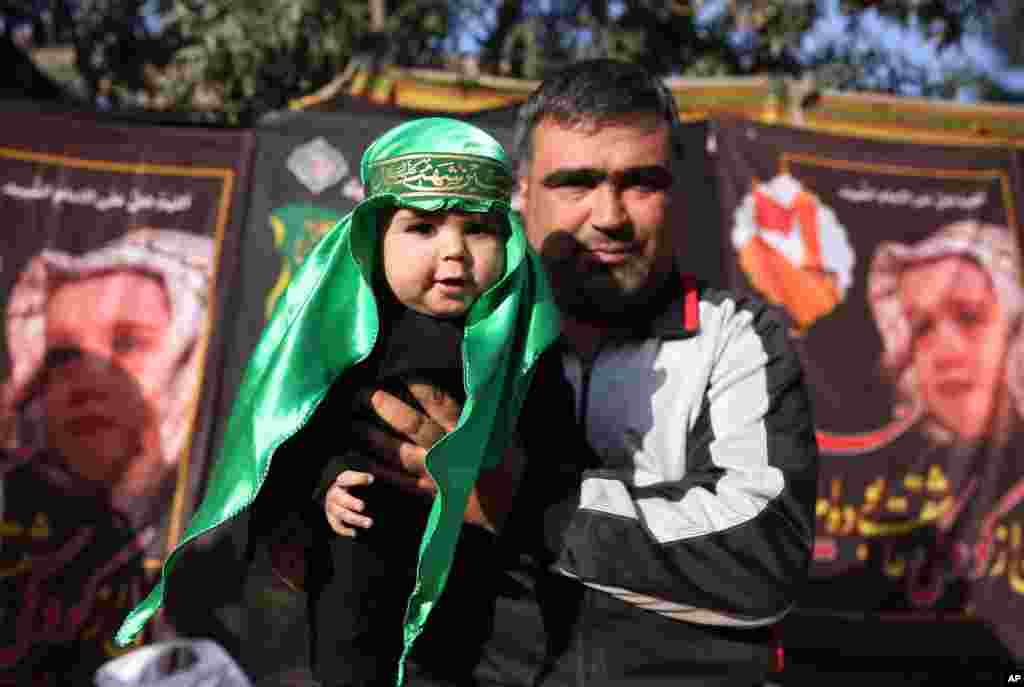 A Shiite Muslim man holds up his baby, dressed in Arabic garb, during a procession to mark Ashoura, in Kabul, Afghanistan.