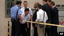 Pengacara Shang Baojun (dua dari kiri) yang mewakili Liu Hui, ipar pemenang Nobel perdamaian Liu Xiaobo dibatasi dengan garis pengaman polisi untuk memberikan keterangan kepada diplomat asing yang berkumpul di luar gedung pengadilan di Bijing, China (16/8). Pengadilan China menetapkan mempertahankan hukuman 11 tahun penjara atas Liu Hui karena kasus penggelapan uang.