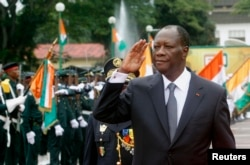 FILE - Ivory Coast's President Alassane Ouattara salutes during a parade to commemorate the country's 54th Independence Day, outside the presidential palace in Abidjan, August 7, 2014.