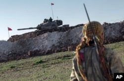 FILE - A Syrian Kurdish militia member of the YPG patrols near a Turkish army tank as Turks work to build a new Ottoman tomb in the background in Esme village in Syria's Aleppo province, Feb. 22, 2015.