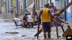 In a photo released by Granma, men play dominoes in the middle of a flooded street as others pull broken furniture from calf-high water in the aftermath Hurricane Irma, in Havana, Cuba, Sept. 10, 2017.