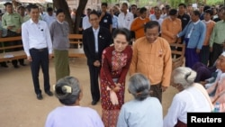 FILE - Myanmar's State Counsellor Aung San Suu Kyi talks to the elderly at a peace talk conference in May Tain Kan village, Wundwin, in Mandalay Division, Aug. 7, 2017.