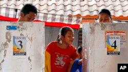 Seorang anak menunggu orangtuanya mengisi surat suara dalam Pilfers di sebuah TPS di Bali, 9 Juli 2014 (Foto: dok).