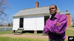 FILE - Rev. Alfred L. Jones III poses in front of the reconstructed slave quarters behind the McLean House on the grounds of Appomattox Court House National Historical Park in Appomattox, Va., April 1, 2015.