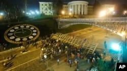 Para demonstran berusaha menembus barikade di Lapangan Independen di ibukota Kiev hari Senin (2/12).