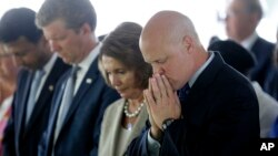 FILE - From right, New Orleans Mayor Mitch Landrieu and House Minority Leader Nancy Pelosi listen to an invocation at a wreath-laying ceremony at the Hurricane Katrina Memorial on the 10th anniversary of Hurricane Katrina in New Orleans, Aug. 29, 2015.