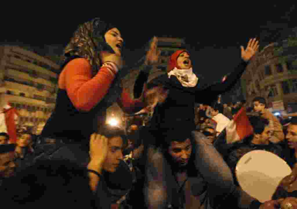 Two Egyptian women celebrate after President Hosni Mubarak resigned and handed power to the military at Tahrir Square, in Cairo, Egypt, Friday, Feb. 11, 2011. Egypt exploded with joy, tears, and relief after pro-democracy protesters brought down President
