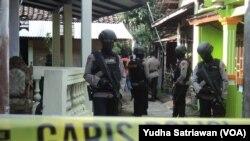 Polisi bersenjata lengkap tengah berjaga saat akan melakukan penggeledahan di sebuah TKP (Foto: ilustrasi).