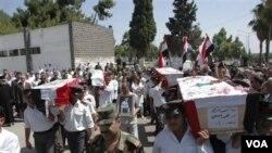Para polisi Suriah memakamkan rekan-rekannya yang menjadi korban dalam bentrokan di kota Homs (18/7).