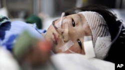 Xiang Weiyi lies in a hospital bed after she was the last survivor rescued some 21 hours after a Chinese high-speed train crash in eastern China's Zhejiang province, July 25, 2011
