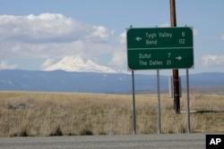 FILE - This sign near Dufur, Oregon, shows distances to the nearest towns, March 20, 2020. Rural residents fear the spread of coronavirus to areas with scarce medical resources.