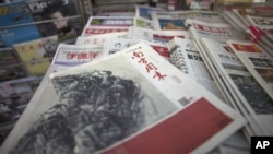 A New Year edition of Southern Weekly, center, published on January 3, 2013, is exhibited at a newsstand in Beijing, China, January 4, 2013.
