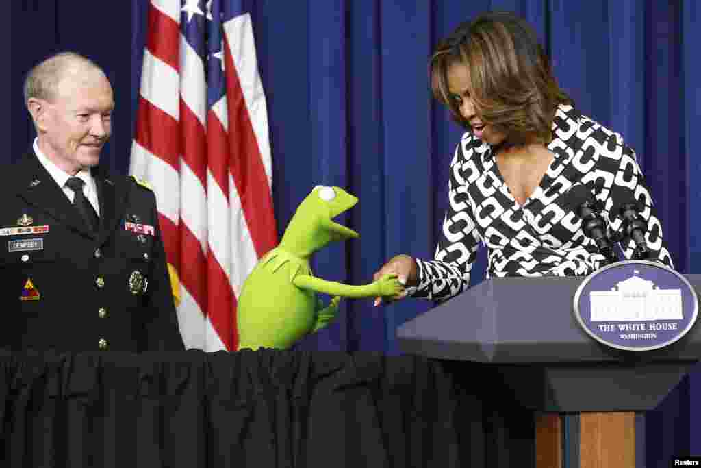 "U.S. First Lady Michelle Obama greets Kermit the Frog as Chairman of the Joint Chiefs of Staff U.S. Army General Martin Dempsey introduces a showing of the new movie ""Muppets Most Wanted"" at the White House in Washington, Mar. 12, 2014."