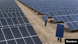 工人在中国新疆搬运太阳能板。美国政府曾于2012年以低价倾销为由对中国太阳能生产商收取惩罚性关税。(资料图片)