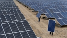 FILE - Employees carry solar panels at a solar power plant in Aksu, Xinjiang Uyghur Autonomous Region, May 18, 2012.