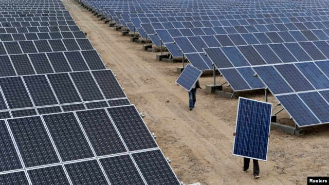Employees carry solar panels at a solar power plant in Xinjiang, China (2012 photo)