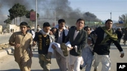 Afghans carrying a man, who got wounded following an attack on UN's office during a demonstration to condemn the burning of a copy of the Muslim holy book by a Florida pastor, in Mazar-i- Sharif north of Kabul, Afghanistan on April. 1, 2011.