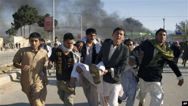 Afghans carry a wounded man following an attack on the UN office during a protest against the burning of a copy of the Quran by a Florida pastor, Mazar-e-Sharif, Afghanistan, Friday, April. 1, 2011.