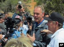 FILE - Interior Secretary Ryan Zinke, second from right, speaks during a press conference near Blanding, Utah, May 8, 2017.