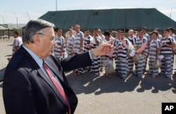 FILE - Maricopa County Sheriff Joe Arpaio, left, orders approximately 200 convicted illegal immigrants handcuffed together and moved into a separate area of Tent City in Phoenix, Arizona, Feb. 4, 2009.