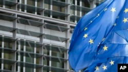 FILE - European Union flags flap in the wind outside EU headquarters in Brussels.