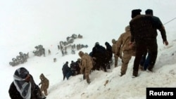 Turkish soldiers and locals try to rescue people trapped under avalanche in Bahcesaray in Van province, Turkey,