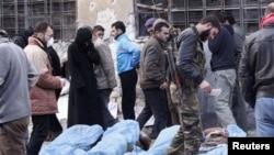 Des combattants de l'Armée syrienne libre et les habitants tentent d'identifier les corps trouvés le long d'une rivière, dans une école utilisée comme un hôpital de campagne à Bustan al-Qasr d'Alep, 29 janvier 2013.