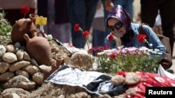 A woman mourns at graves for miners who died in Tuesday's mine disaster, at a cemetery in Soma, Turkey, May 18, 2014.