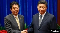 安倍晉三與習近平2014年11月10日在北京出席亞太經合會期間見面握手(資料圖片)