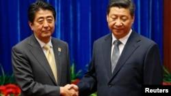 លោក Shinzo Abe នាយករដ្ឋមន្ត្រីជប៉ុន (ឆ្វេង) និងលោក Xi Jinping ប្រធានាធិបតីចិន (ស្តាំ) ចាប់រលាក់ដៃគ្នាក្នុងពេលជួបគ្នាក្នុងកិច្ចប្រជុំ APEC នៅទីក្រុងប៉េកាំងនៅថ្ងៃទី ១០ ខែវិច្ឆិកា ឆ្នាំ២០១៤។