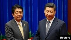 日本首相安倍晉三與中國國家主席習近平2014年11月在北京亞太經合會期間會面握手時的神態 (資料圖片)