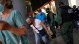 Los residentes pasan por debajo de una tira de cinta adhesiva que sirve como barrera mientras se dirigen a un área donde se les inyectará una segunda dosis de la vacuna Sputnik V COVID-19 en Caracas. Septiembre 21, 2021.