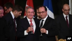FILE - Cuban President Raul Castro (L) and French President Francois Hollande raise a glass during a state dinner at the Elysee Presidential Palace in Paris, France, Feb. 1, 2016. Castro also received a warm welcome from French business leaders.