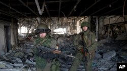 Russia-backed rebels walk in the destroyed building of the airport outside Donetsk, Ukraine, Wednesday, Feb. 25, 2015.