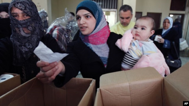 Syrian refugees receive humanitarian aid from an Islamic organization in Tripoli, Lebanon, March 6, 2012.