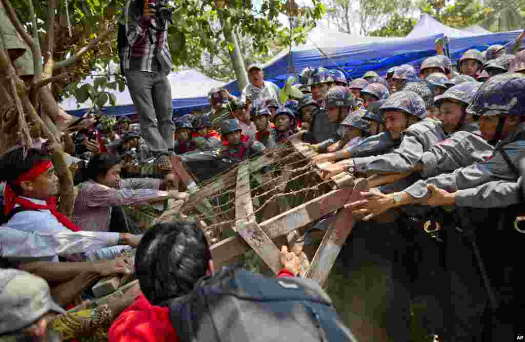 Student protesters struggle with riot police to remove a barricade installed by police during a protest in Letpadan, Myanmar, March 10, 2015.