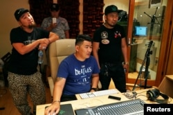 Hip-hop singers Sanjjav Baatar (L), Battogtokh Odsaikhan of a band called Fish Symboled Stamp and a sound engineer adjust a mixing console in a recording studio in Ulaanbaatar, Mongolia, June 24, 2017.